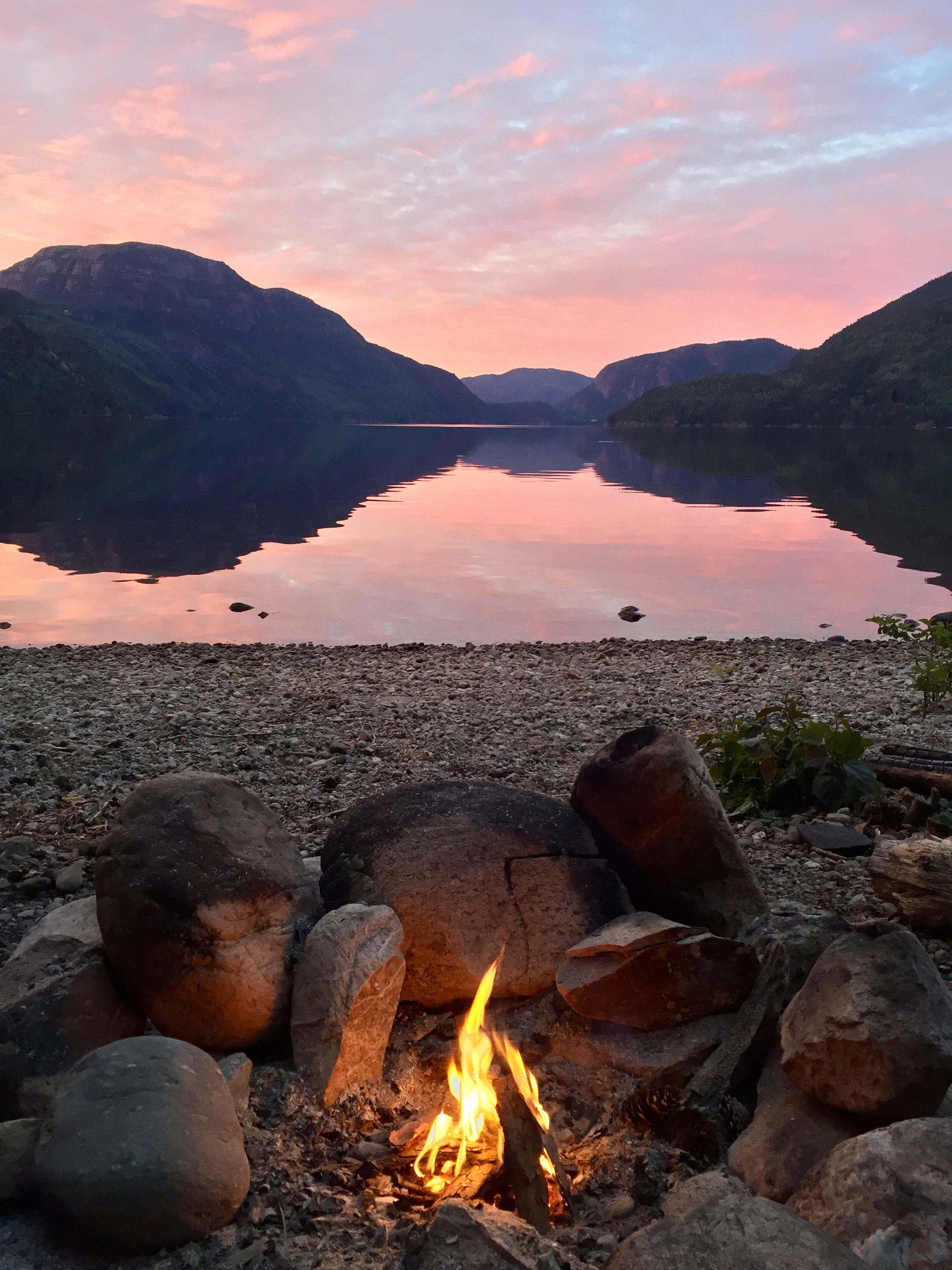 A campfire, looking out over the water early in the morning